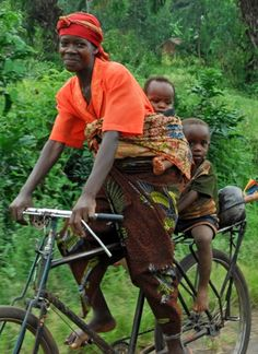 Burundi, Africa.  A previous pinner said:  In my era in Kenya, you never saw a woman on a bicycle.  Well, this is Burundi, but it does cause me to wonder if it's customary in other parts of Africa.