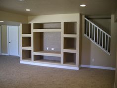 open stairs with support beam built in entertainment center. Only issue I see is that you would really have to like that spot for your tv and such to go ahead and build it in. Other than that, this rocks.