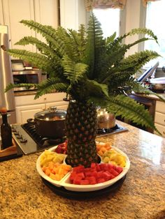 Hollowed out pineapples and a fern (fake?) to make a palmtree centerpiece.