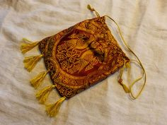 14th c. alms purse from Neues aus der Gotik blog (in German) - for just the right piece of silk cloth (and be sure to buy matching/contrasting silk thread for the tassels cords)