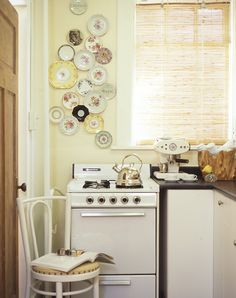 An otherwise plain corner in this compact kitchen is enlivened with a whimsical collection of pretty patterned plates displayed on wall-mounted plate hangers.