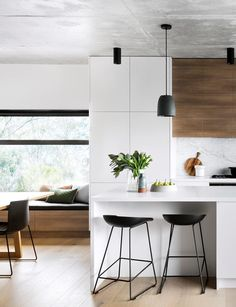 This modern kitchen has a timeless white palette with natural stone and timber.