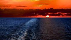 海上での覚醒船の後ろの美しい夕日 夕焼けや朝焼け 自然 高解像度で壁紙