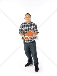 holding football - A smiling young boy holding a football