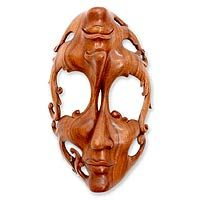 """Wood mask, 'Joy and Sorrow'  """"Happiness and sadness are like twins who are very close. Once you are happy, you know that whatever made you happy is something that will also make you sad. So we just have to remember that all feelings are finally the same,"""" says Wayan Rendah. To express the concept, he sculpts an exquisite mask from Balinese suar wood. One side is joyous while the other is sad."""