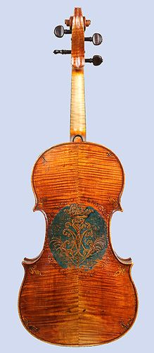 Viola by Andrea Amati, Cremona, ca. 1560. Gilt paintings of fleurs-de-lis & trefoils on  back, surrounding monogram believed to be  of Marguerite de Valois-Angoulême. The Latin motto may relate to the court of King Philip II of Spain. Instrument was reduced in length & width from original size