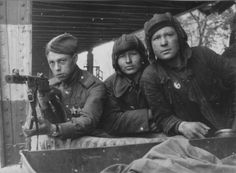 Three Soviet soldiers in Berlin. On the left breast soldier with a submachine gun - two Orders of Glory.