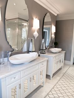 Amazing bathroom with dual white mirror paneled vanities topped with marble counters and modern vessel sinks with waterfall faucets. Carrara, White Mirror, White Vanity, Grey Wall Color, Arabesque Tile, Dark Grey Walls, Mosaic Bathroom, Grey Bathrooms, Master Bathroom