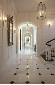 White walls. Faux Marble floor. Black and white stair case. Arches.