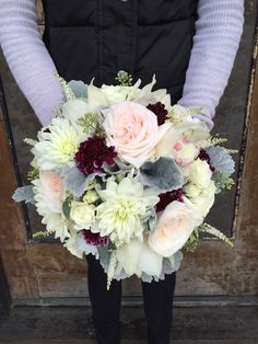 Wedding bouquet featuring dusty miller, white dahlias, scabiosa, and garden roses.