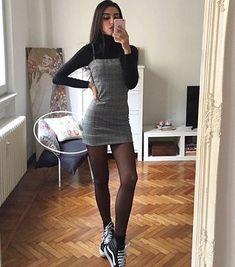 Alerta de tendência: vestido xadrez. Blusa preta de gola alta, vestido cinza de alcinha, meia calça preta, tênis vans preto