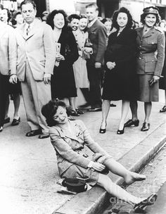 Nylon stockings. Woman in the street putting on nylon stockings in the USA after World War II. Nylon was a new material discovered by the DuPont Company in 1935 and used from 1939 in products such as stockings. Nylon stockings were immensely popular, but had to be discontinued due to nylon being reserved solely for wartime applications. When nylon was once again allowed for the domestic market, women were eager to start wearing them again and queued in sales such as this one. Photographed in…