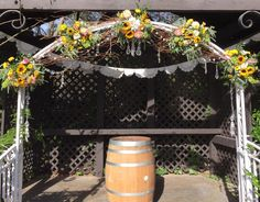 Wedding arch using, twisted willow, crystal garland, flower sprays including, sunflowers, English roses, dahlias and seeded eucalyptus.