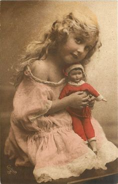 girl sits with doll on lap, facing right, looks front & up