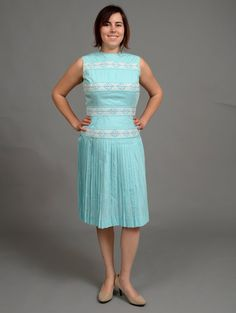($42.00) This lovely 1960s dress is the perfect thing for a sunny afternoon. This dress features a high neck, pleated skirt, and crocheted flower details. Made of lightweight fabric, this dress will keep you cool while looking vintage chic.  This dress fits like a women's Small (2/4). Measurements: Bust- 34in Waist- 26in Hip- 32in  The model shown is a women's 6/8. The dress did not zip up on the model.