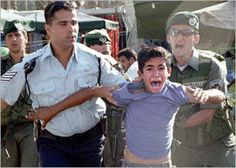 This young Palestinian boy is completely frightened by two Israeli soldiers, who abuses the boy unceremoniously.