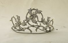 ORCHID TIARA in natural pearls and diamonds c1860. Designed as 3 stylized interlocking orchids pavé-set with rose-cut diamonds and natural pearl accents, detachable into 3 brooches, fittings included. This tiara was first worn in 1860 by Baroness Helen Sina at her wedding to Prince Gregory Ypsilantis.