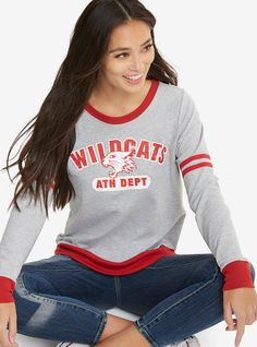 """What team? Wildcats!""   Getcha head in the game with this athletic sweatshirt from  High School Musical . The grey and red trimmed pullover has the Wildcats logo on front with distressed text design. You'll really have it going on when you wear it.    Officially licensed by Her Universe  48% polyester; 52% cotton  Wash cold; dry low  Model is wearing size small  Made in USA  Listed in junior sizes"