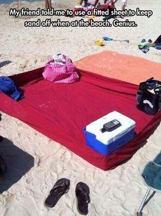 Usando una sabana para ir a la playa en vez de toalla, y cercando las puntas con bolsas e igloo