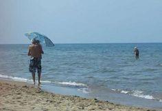 Nonno protegge nipote dal sole con ombrellone