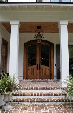 Beautiful southern cottage designed by Bob Chatham and built in Fairhope, AL by Scott Norman. Front Entry Columns Covered Porch Split Brick Floor Exposed Wood Ceiling French Doors Shutters | www.bobchatham.com | Copyright by Designer.