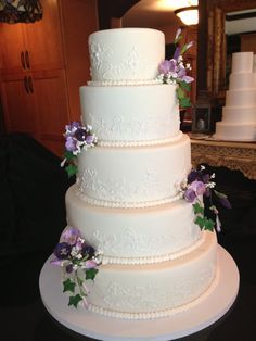 5 tier ivory wedding cake with brushed icing embroidery. Accented with sugar freesia in purple tones, ivy and baby's breath. Made by: Sonia Ackley.