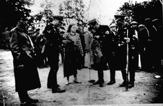 Armed German SS men in a Lithuanian city, inspecting the clothes of a Jewish woman.