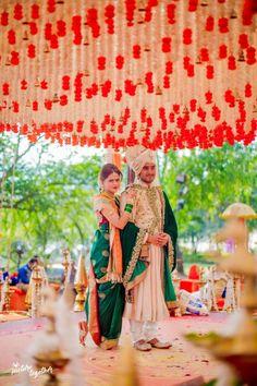 South Indian Decor - Hanging Floral White and Red Decor with the Bride in a Green Kanjivaram and Groom in an Off White Sherwani  #wedmegood #indianbride #indianwedding #bridal #groomshot #candidcoupleshot #weddingdecor #mandapdecor