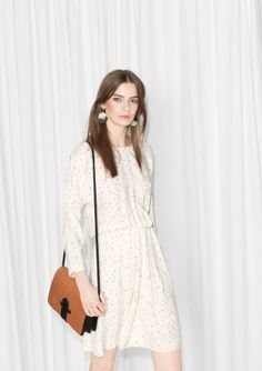 Elasticated waist blouses gracefully the long-sleeved bodice of this free-and-easy printed dress accented with a keyhole slit at back.