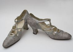 "c 1923-27  flapper silver brocade evening shoes fashioned from metallic silver damask woven w/ a floral rose pattern. T-strap & cutwork pattern are silver kid leather. Complex ""cutwork apron"" style; shapely Louis heels 2 1/2"" high; straps close w/ small silver buttons -  show gentle wear - $ 350"
