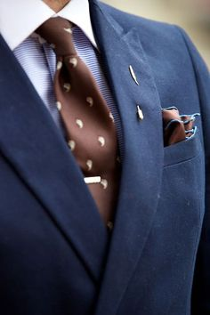 Navy jacket, light blue shirt with contrast collar, brown tie