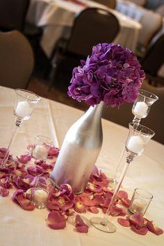 Purple hydrangea centerpiece, silver wine bottles, tiered glass votives, purple petals