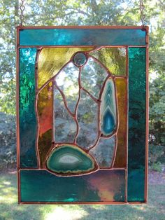 The Cove is approximately 7.5 inches x 10.0 inches and contains a two polished teal agates. Stained glass colors include teal, iridized teal,