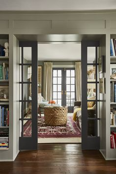 New French doors invite daylight to flow through the den and the living room while pocket doors between the rooms slide closed for sound control. Paint: Farrow & Ball's Down Pipe (pocket doors