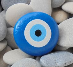 Evil Eye Painted Stone ! Is Painted on a round smooth stone with Acrilic paints and covert with varnish protection by RockArtAttack on Etsy https://www.etsy.com/listing/225840296/evil-eye-painted-stone-is-painted-on-a
