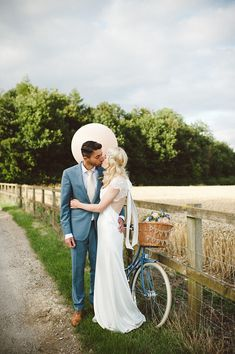 Stunning real bride Emma wearing David Fielden with a beautiful open lace back for her country wedding! Here she is kissing her new husband amongst wheat fields and a blue vintage bike. Dress from Carina Baverstock Couture in Bradford on Avon. Lace Wedding Dress With Sleeves, Wedding Flower Girl Dresses, Luxury Wedding Dress, Country Wedding Dresses, Wedding Dresses Plus Size, Designer Wedding Dresses, Bike Wedding, Barn Wedding Venue, Wedding Blog