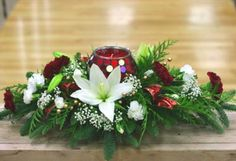 The festive Christmas floral centerpiece includes carnations, lilies, babies breath, white pine, noble fir, cedar, berries, ribbon flips and accented a warm red candle in the center. Candle style may vary.