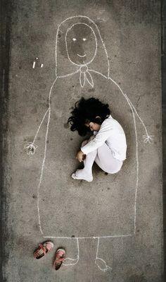 Ребенок лежит в объятиях рисунка погибшей во время войны матери, которую он нарисовал во дворе детского дома. Из уважения даже к рисунку своей матери, он снял обувь.