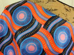 African Wax Print Fabric--Ankara Print Fabric--Genuine Vlisco Voila for You--Orange & Periwinkle Wheels--African Fabric by the HALF YARD by MoreLoveMama on Etsy https://www.etsy.com/listing/493306993/african-wax-print-fabric-ankara-print