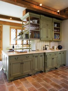 Sage Green Kitchen Cabinets.  I like the sink which is extended out a little from the rest of the cupboards with the accent corners.