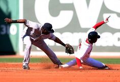 BOSTON, MA - SEPTEMBER 27: Rusney Castillo #38 of the Boston Red Sox steals against Jose Pirela #67 of the New York Yankees during a game at Fenway Park on September 27, 2014 in Boston, Massachusetts. (Photo by Elsa/Getty Images)