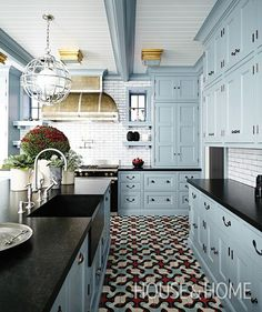 """From the blue and rust cement floor tiles to the professional French range and caged light fixture, there's not one feature that doesn't scream """"wow.""""   Photographer: Angus Fergusson   Designer: James Davie"""