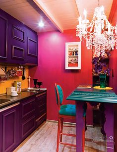 Purple, fuchsia, and turquoise kitchen with a crystal chandelier.