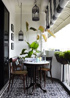 Classy balcony with black and white patterned tile, antique bistro set, lanterns, planters, and sun shading awing and roller shade