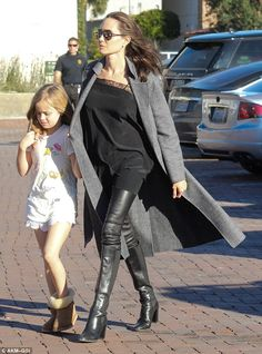 Mom's girl: Vivienne, in white shorts and a funky t-shirt with shearling boots, stayed close to her mom walking with Angelina's arm around her shoulder and holding her hand