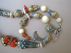 """Detail view of """"Mermaid's Gift"""" by ©Myra Schwartz.  sterling mermaid toggle, glass beads, pearls, mother of pearl, antique Coral and artisan lampworked glass beads. This piece has been sold."""