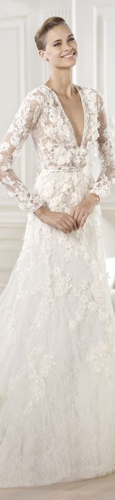 Chantilly lace dress with crystal gemstone embroidery and organza flower appliqués. V-neck and long sleeves with sheer appearance. The waist is encircled by a fine mikado silk belt. Flared skirt with appliqués cascading down to the hem. http://www.pronovias.com/wedding-dresses-elie-by-elie-saab-collection-2014-crux