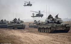 War zone: Apache helicopters hover above a column of Army vehicles including Challenger 2 tanks as they take part in an exercise on Salisbury Plain, Wiltshire