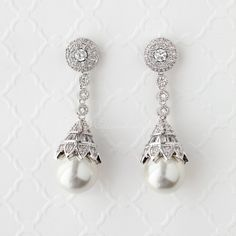 Beautifully designed antique cubic zirconia earrings with a teardrop pearl drop. Each pearl has a floral styled cap of tapered baguettes and round CZ jewels. These earrings will make a statement at any formal event. Pierced post backs and 1.75 inches long. Rhodium plated, grade AAA cubic zirconia, 12mm glass pearls and lead free.