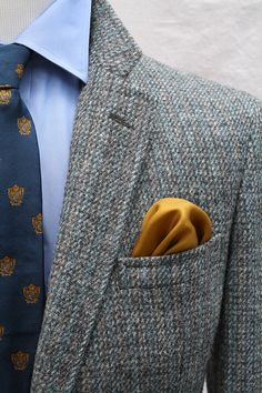Grey tweed sport coat, light blue shirt, blue tie